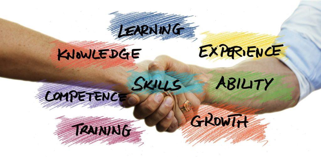 """Mains se serrant avec le mot skills"""" pour """"compétences"""" au milieu."""