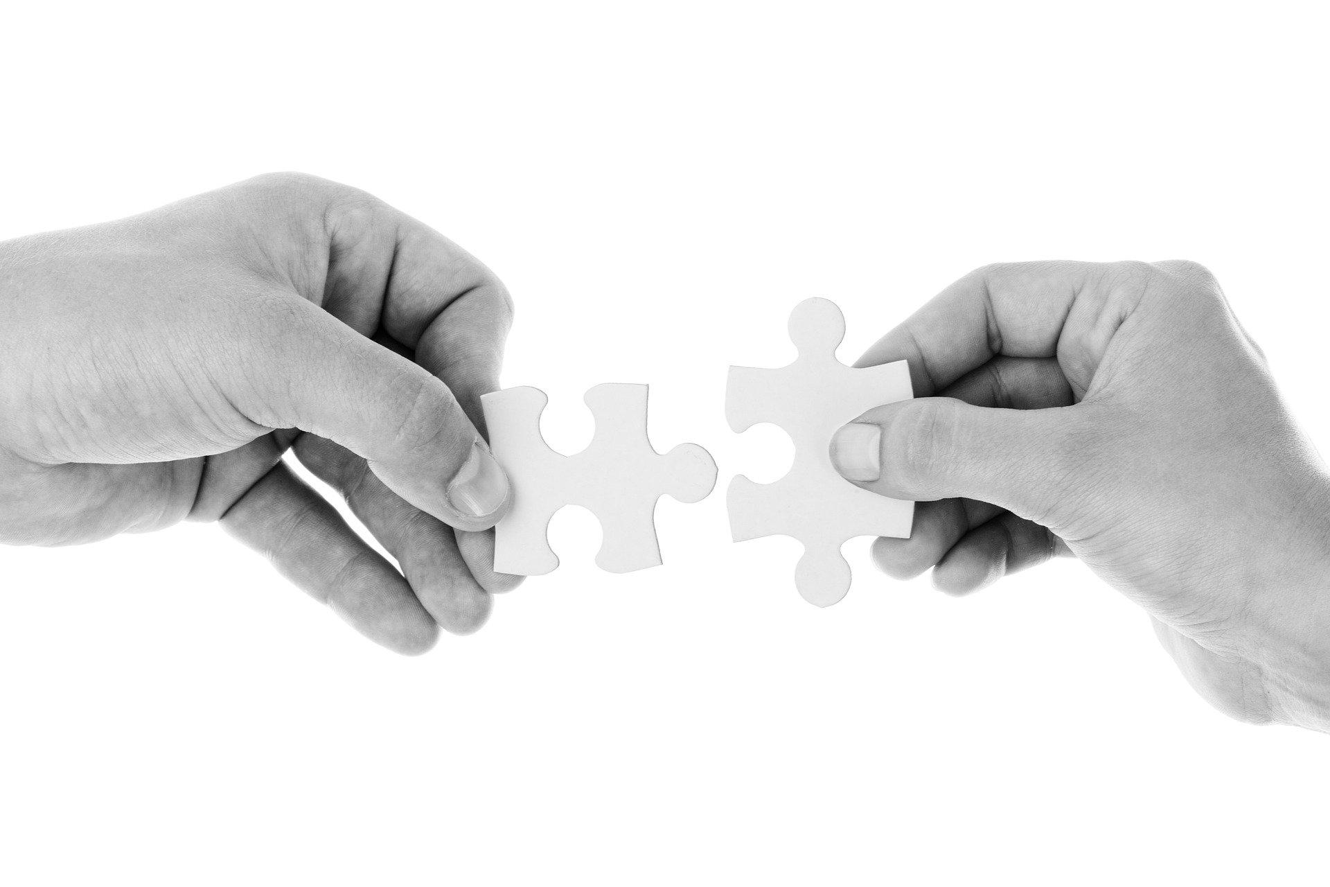Mains assemblant deux pièces de puzzle grâce à l'aide apportée par le coach.