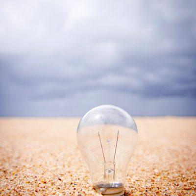 Ampoule plantée dans le sable, symbolisant un nouveau départ avec le coaching de transition.