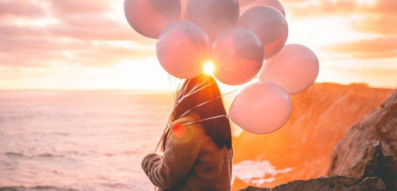Jeunes filles avec des ballons regardant la mer, pour symboliser une nouvelle façon de penser avec le coaching de transition.