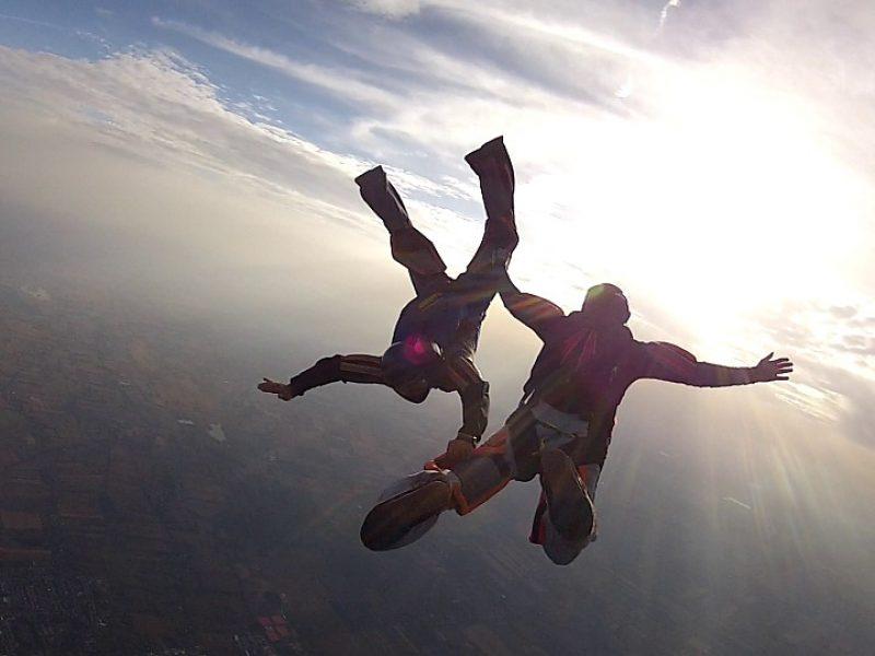 Deux personnes sautant en parachute, symbolisant l'évolution en équipe.