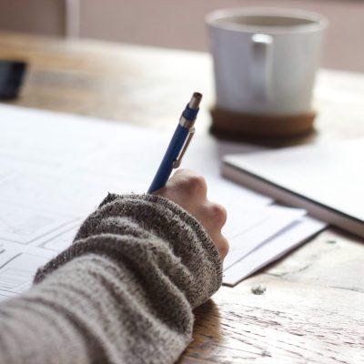 Femme prenant des notes, en écrivant à la main, lors d'une formation.