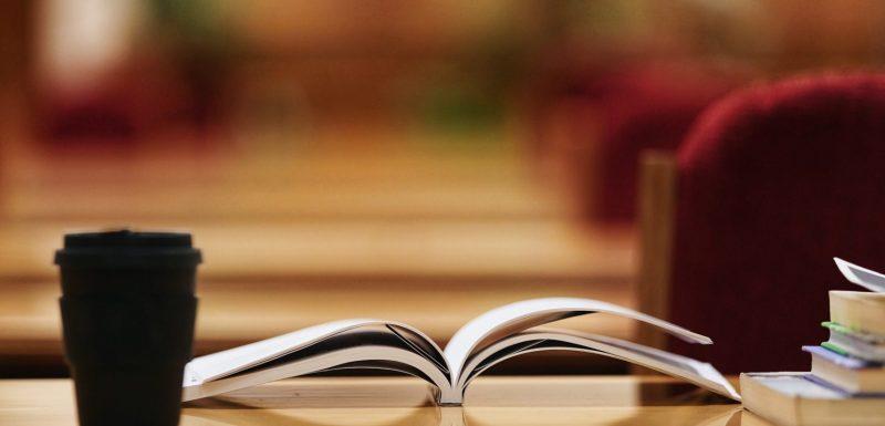 Livre ouvert sur une table, symbole de l'apprentissage.