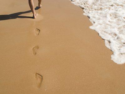 Personne marchant dans le sable, symbole d'une approche réflexive.