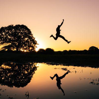 Personne sautant par-dessus une rivière, osant sauter le pas pour avancer professionnellement.