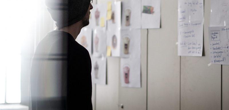 Homme regardant des feuilles de papier sur un mur, nouvelles perspectives de sa vie professionnelle, mises en valeur grâce au coaching de transition.
